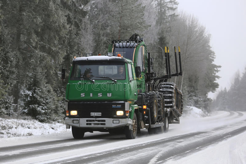 Green Sisu SM300 Truck Hauls Forestry Equipment in Winter stock photography