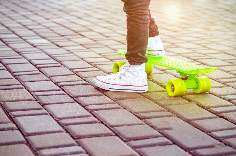Green skateboard and kids sneakers. Outdoors stock image
