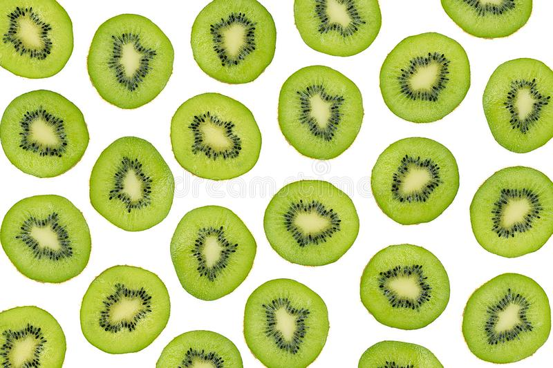 Green slices of kiwi fruit isolated on white background, overhead shot. Sliced kiwi photographic pattern, top view. royalty free stock photography