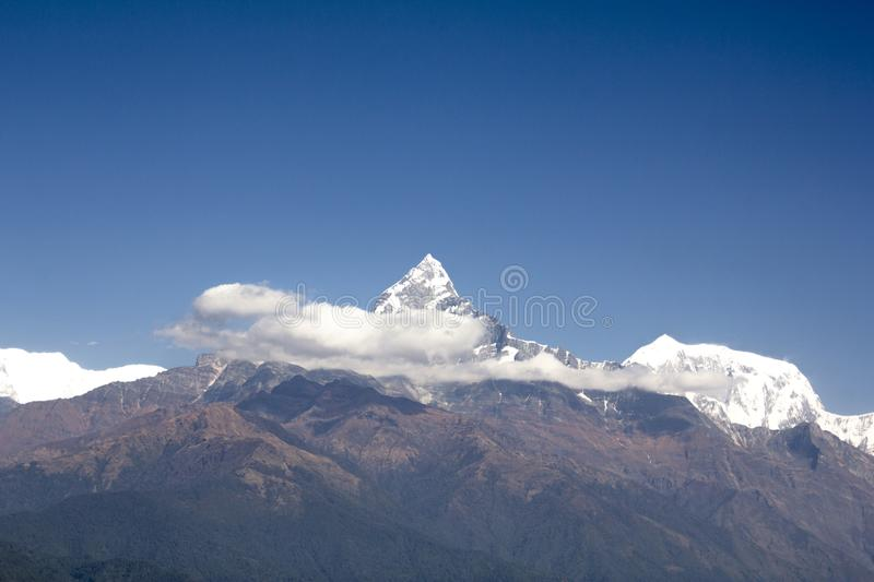 Green slope of Mount Annapurna with a snowy peak Machapuchare and white clouds against a clean blue sky. Nepal Himalayas royalty free stock photography