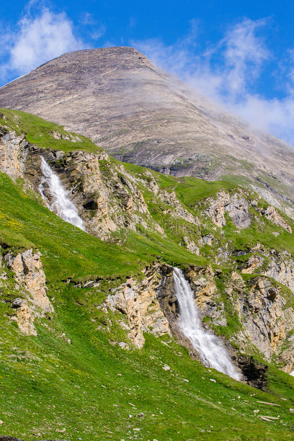 Download Green Slopes With Two Waterfalls And A Mountain Peak Royalty Free Stock Image - Image: 38151356
