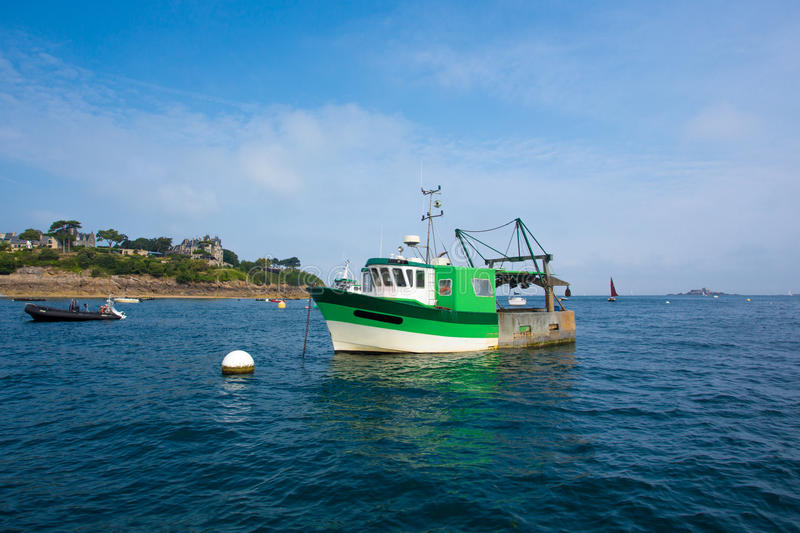 Green small fishing boat in shallow water stock image