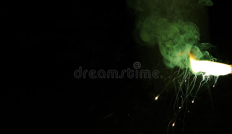 green smoke sparkler on sparkling with dark background with green color smoke on the deepavali royalty free stock photography