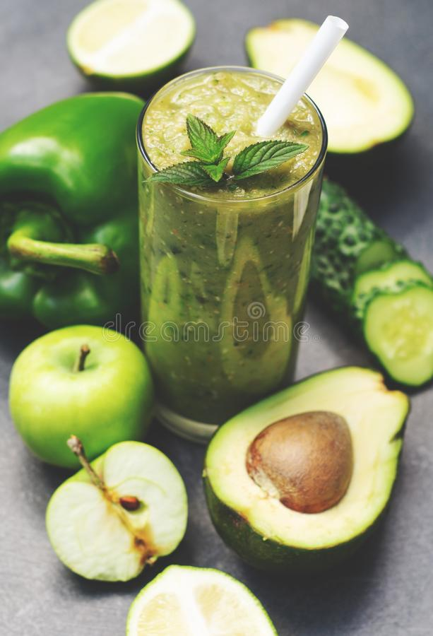 Green smoothie of apple, cucumber, avocado and pepper in a glass. Whole ingredients on a dark background stock images