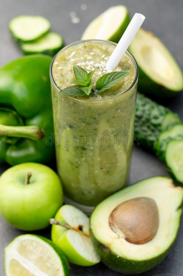 Green smoothie of apple, cucumber, avocado and pepper in a glass. Whole ingredients on a dark background stock photo