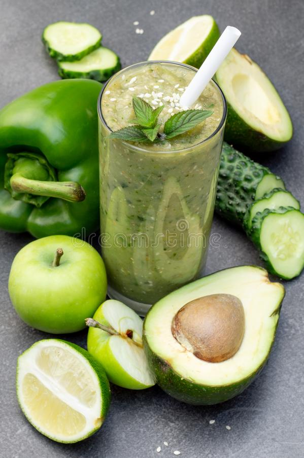 Green smoothie of apple, cucumber, avocado and pepper in a glass. Whole ingredients on a dark background royalty free stock image