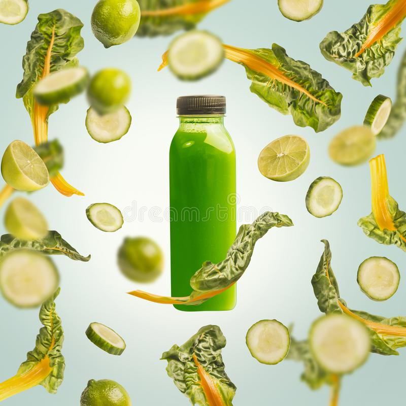 Green smoothie bottle with flying or falling ingredients: citrus fruits, cucumber and chard leaves on light blue background royalty free stock photos