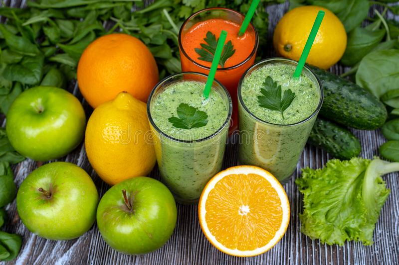 Green smoothie, carrot juice and multicolored fruit, green Apple, cucumber, spinach, lemon, orange, salad, cilantro. On wooden background stock photo