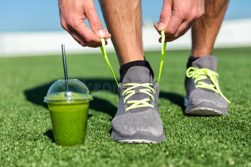 Green smoothie fitness man tying running shoes stock images