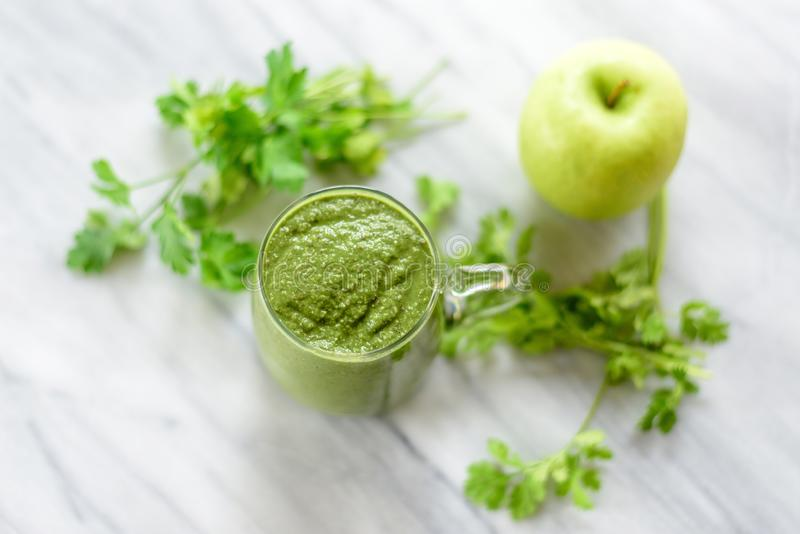 Green smoothie and fresh herbs on marble surface royalty free stock image