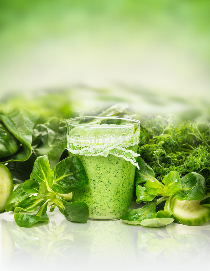 Green smoothie glass over vegetables and herbs. Background royalty free stock image