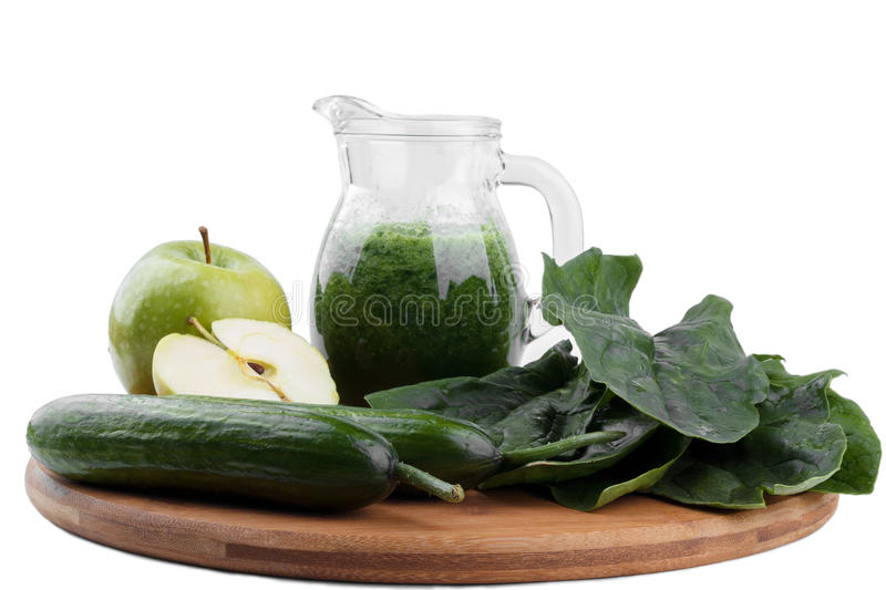 Green smoothie. Healthy green smoothie with spinach,green aple,kiwi and cucumber on cutting board isolated stock photography