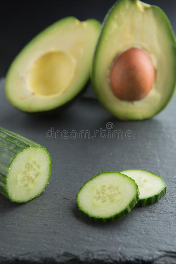 Green smoothie ingredients - avocado, cucumber on a dark background stock images