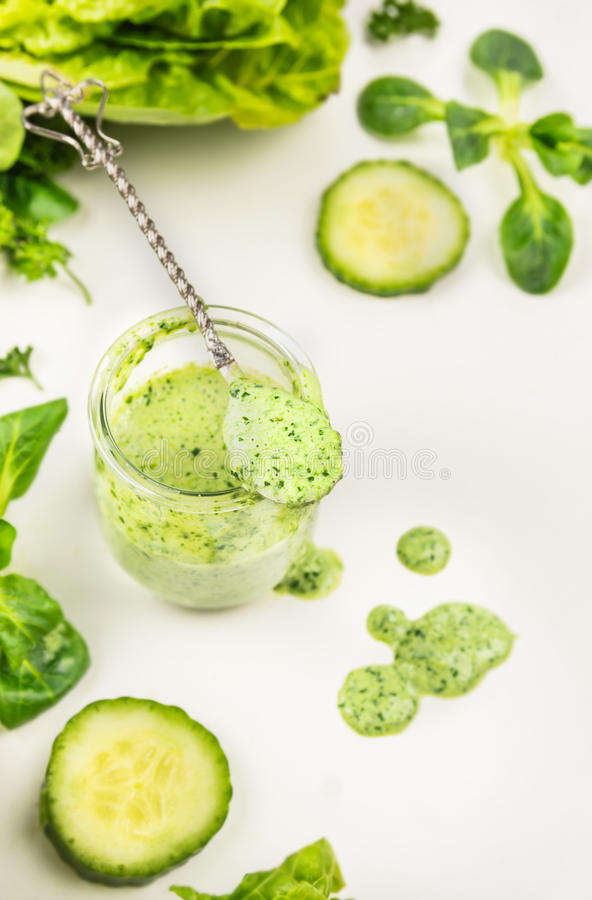 Green smoothie in jar with spoon and vegetables stock photo