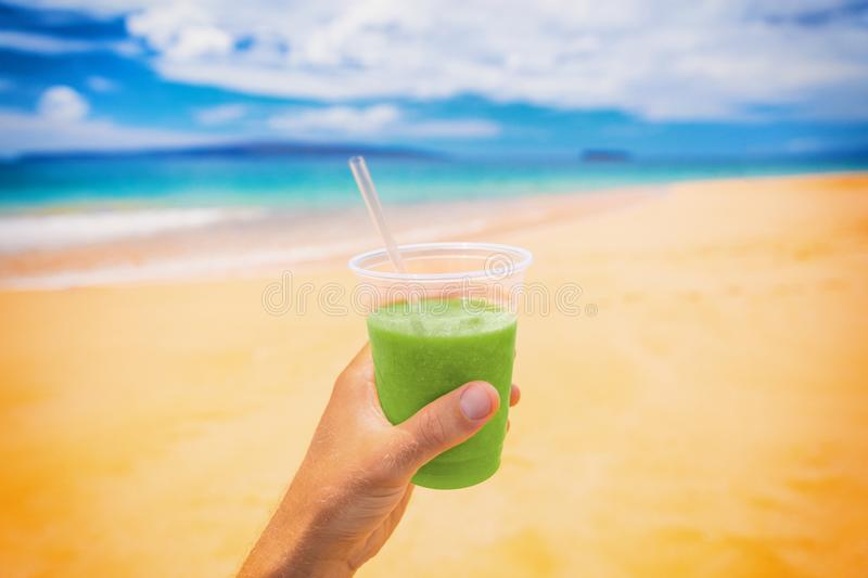 Green smoothie juice detox drink selfie man holding plastic cup on beach summer background. Food picture of healthy nutrition diet royalty free stock image