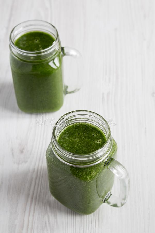 Green smoothie with spinach, avocado and banana in glass jars on a white wooden surface, low angle view. Closeup.  royalty free stock image