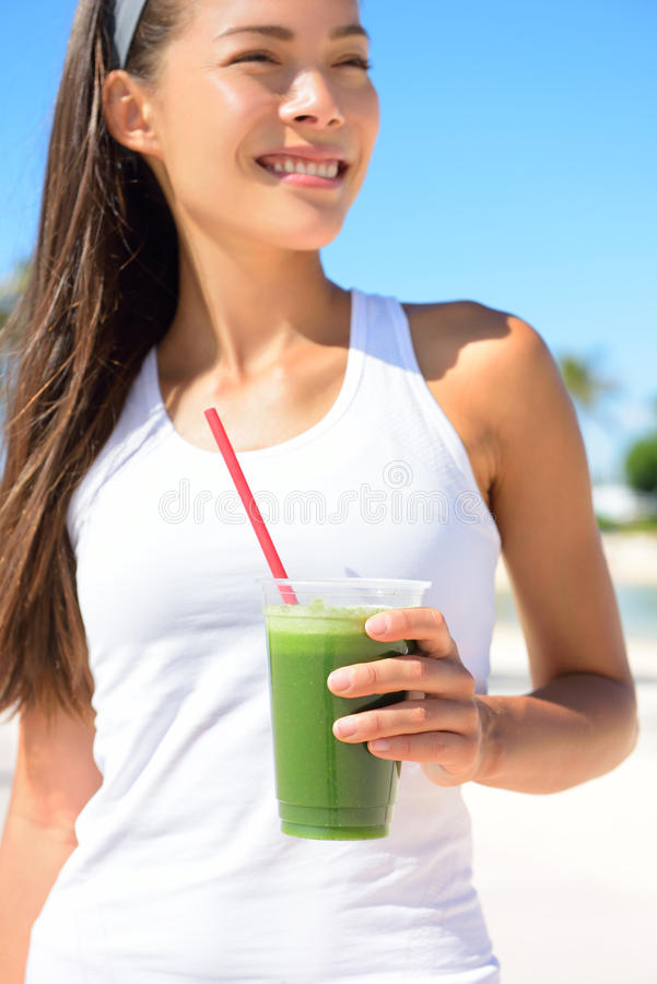 Green smoothie - woman holding detox juice in sun. Green smoothie. Woman holding green vegetable detox juice outside in summer sun. Healthy lifestyle with stock image