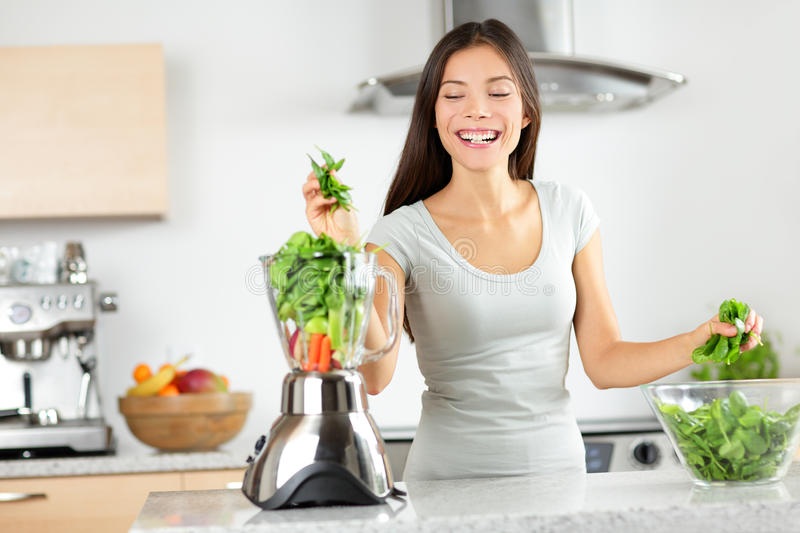 Green smoothie woman making vegetable smoothies. With blender home in kitchen. Healthy eating lifestyle concept portrait of beautiful young woman preparing royalty free stock photography
