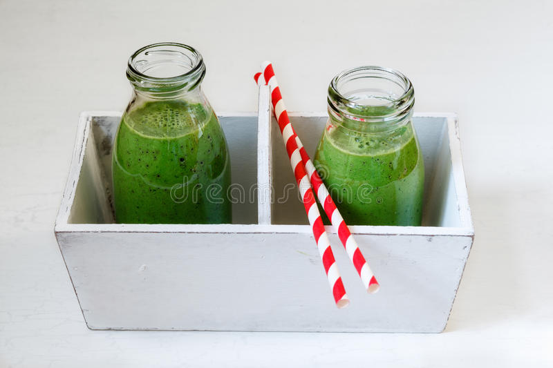 Green smoothies in bottles. With straws in tray royalty free stock photography