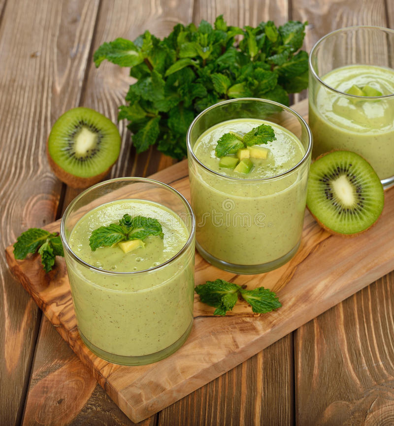 Green smoothies. On a brown background royalty free stock photo