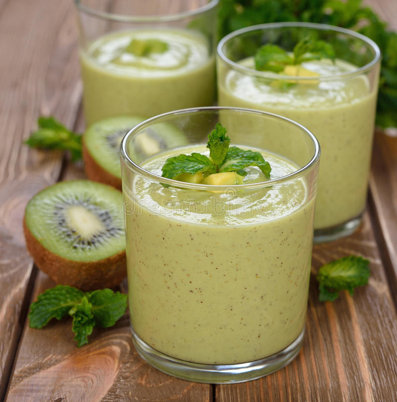 Green smoothies. On a brown background royalty free stock photography