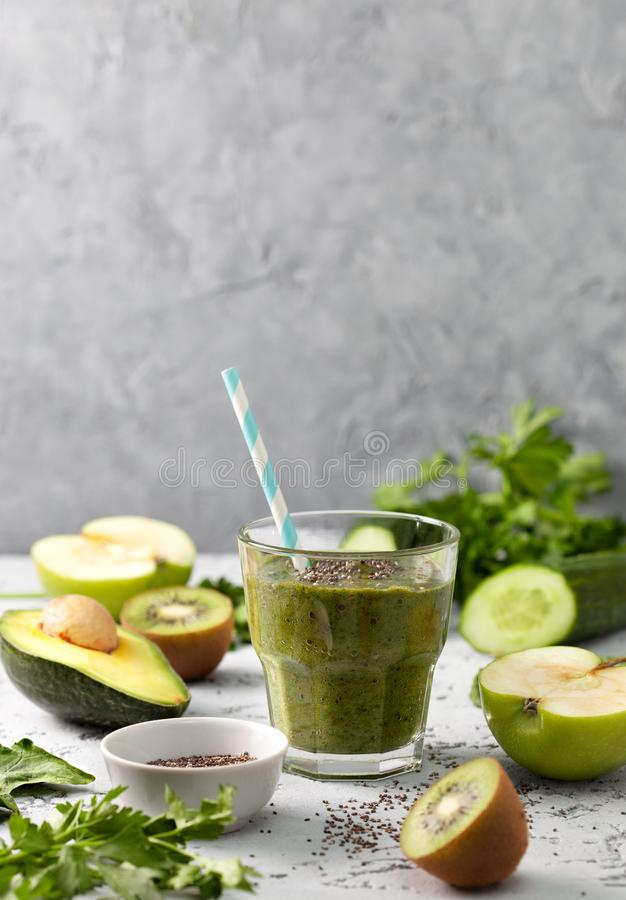 Green smoothies in a glass. Fresh vegetables and fruits on a gray background. copy space stock photography
