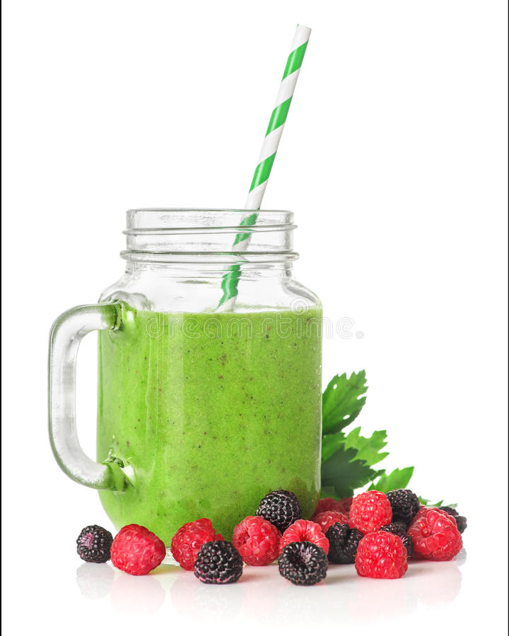 Green smoothies in a glass jar. With raspberries and blackberries, a cocktail stick isolated on white background, healthy eating concept stock photo