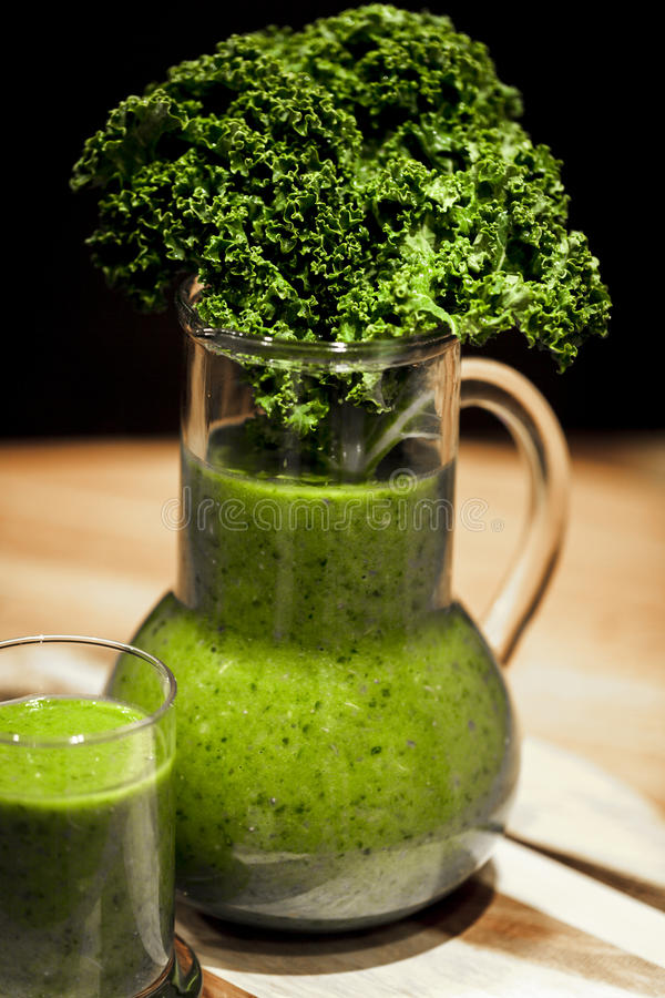 Green smoothies. Healthy green smoothies with organic kale leaves stock photo