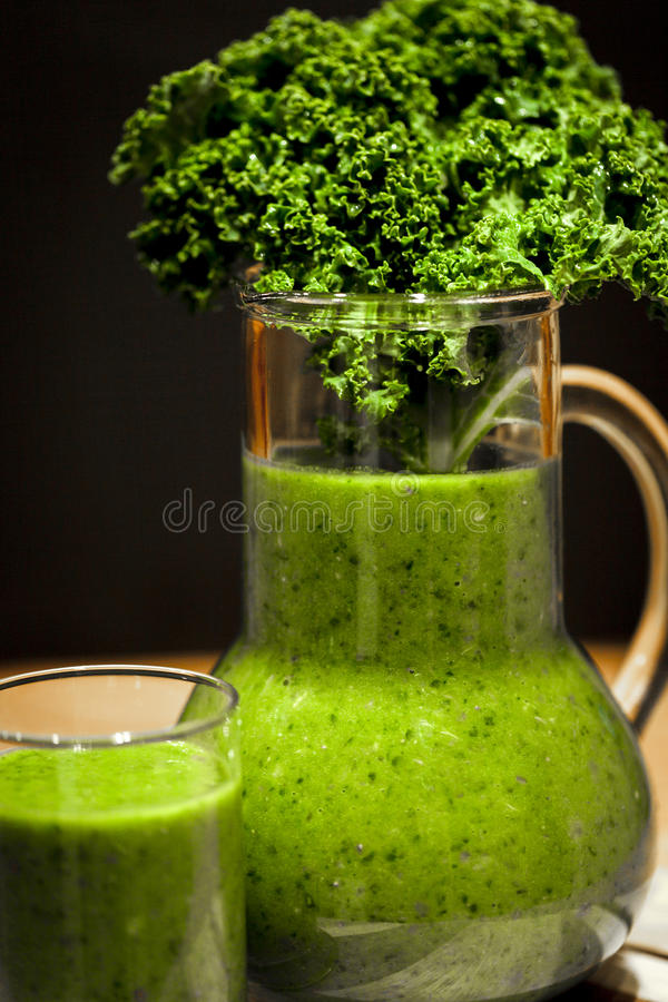 Green smoothies. Healthy green smoothies with organic kale leaves royalty free stock image