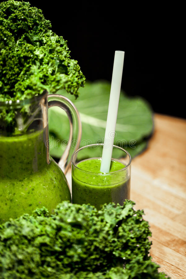 Green smoothies. Healthy green smoothies with organic kale leaves royalty free stock photography