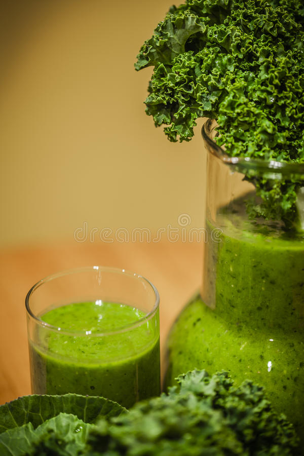 Green smoothies. Healthy green smoothies with organic kale leaves royalty free stock photo