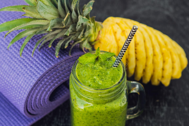 Green smoothies made of spinach and pineapple and a yoga mat. Healthy eating and sports concept stock photos