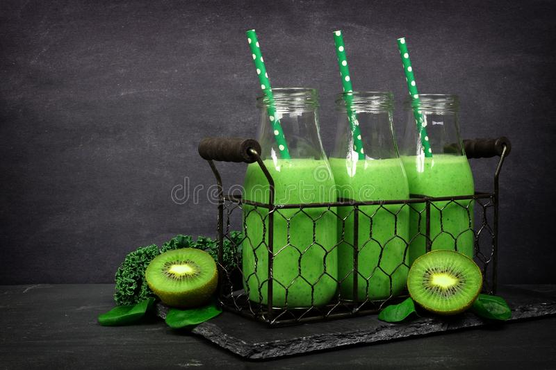 Green smoothies in milk bottles in a vintage basket against slate. Green smoothies in milk bottles in a vintage wire basket against a dark slate background royalty free stock photography