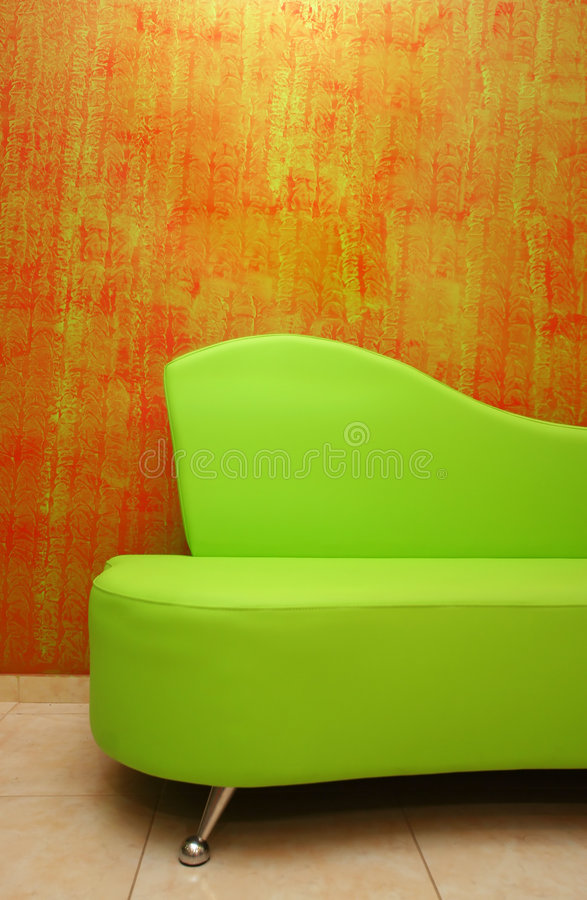 Green sofa. Detail over a stylish red wall-paper stock image
