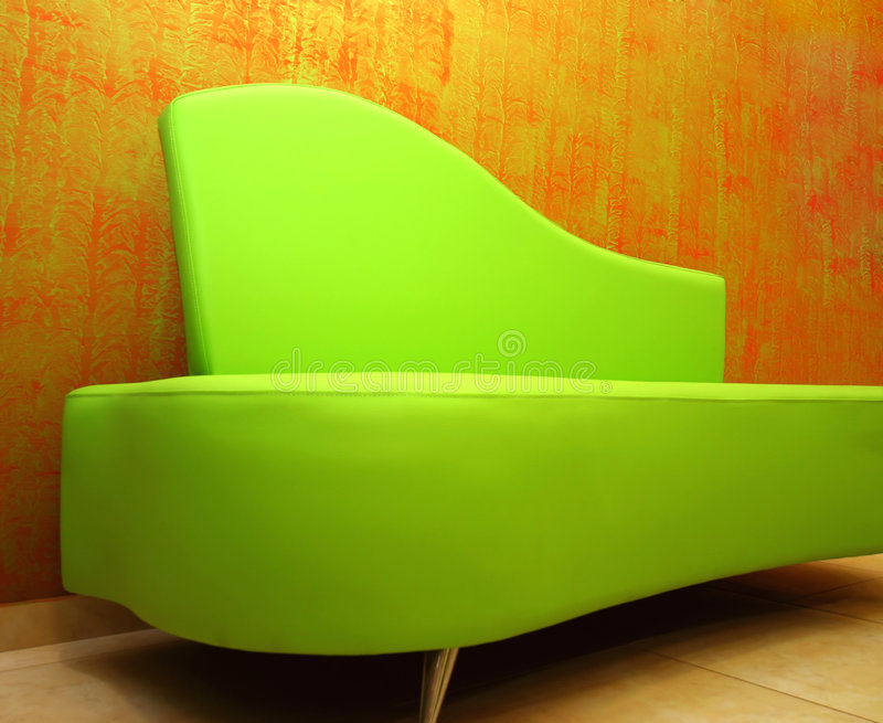 Green sofa. Over a stylish red wall-paper royalty free stock photos