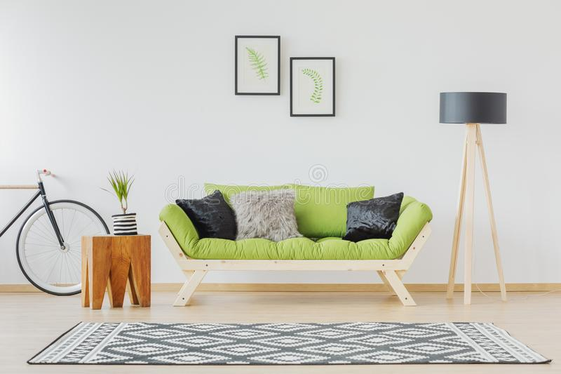 Green sofa and black accent. Scandinavian design of contemporary interior with green sofa, wood and black accents on lamp, bike, pillows and rug royalty free stock photography