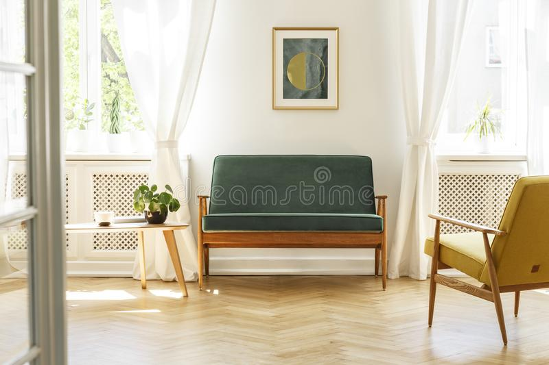 Green sofa with dark, wooden frame and a comfy yellow armchair i. N a white retro living room interior with natural light coming through big windows. Real photo stock photos