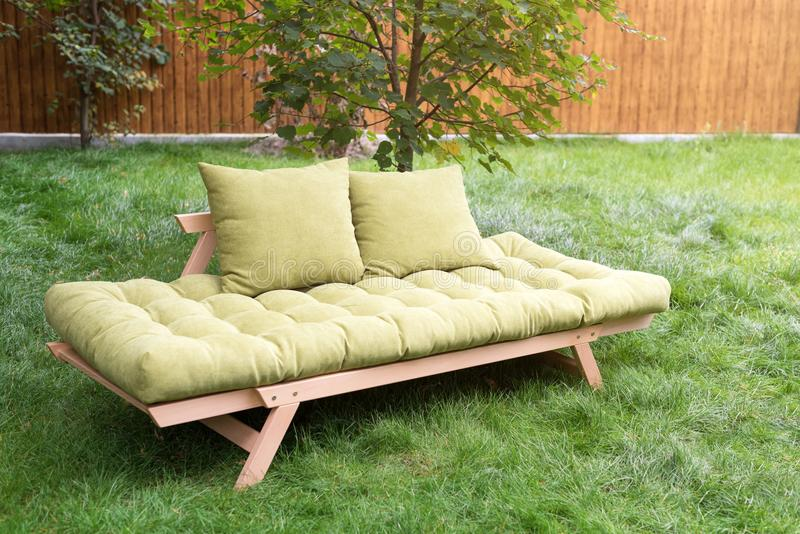 Green sofa in the yard outdoors. Outdoor furniture in green garden patio. Green sofa in the yard outdoors. Outdoor furniture in green garden patio royalty free stock photography