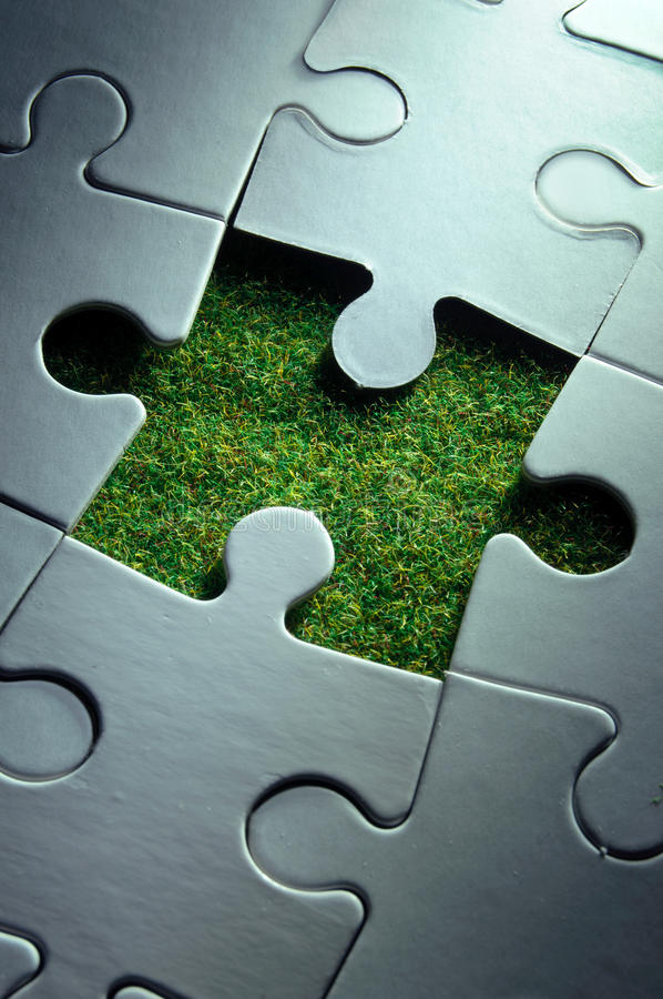Green solutions. Jigsaw piece missing revealing green grass growth stock image