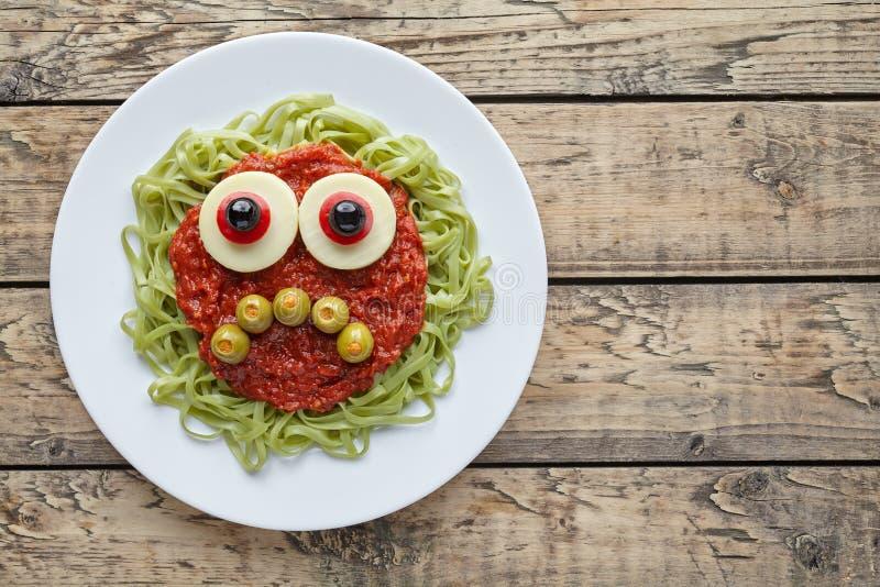 Green spaghetti pasta creative spooky halloween food monster with sad smile. Fake blood tomato sauce and big mozzarella eyeballs holiday decoration kid party royalty free stock image