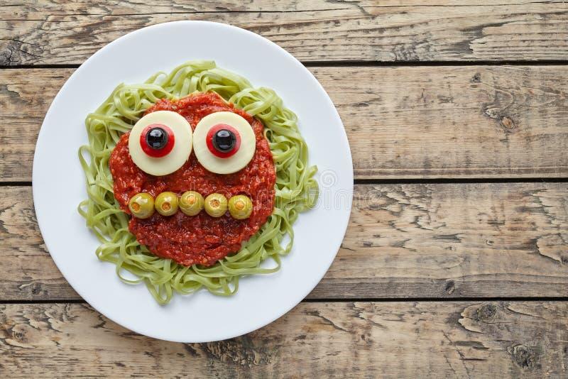 Green spaghetti pasta creative spooky halloween food monster with smile tomato sauce and funny big mozzarella eyeballs royalty free stock photo