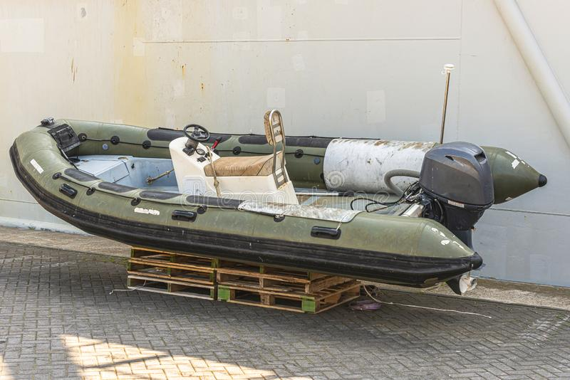 Green speedboat with a outboard motor. Stands on wooden pallets next to a trawler on the quay stock image