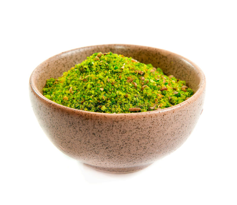Green spices in a ceramic bowl. Green exotic spices in a ceramic bowl isolated on white royalty free stock images