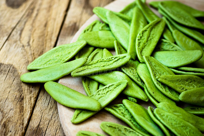 Green spinach italian pasta in the shape of olive leaves, scattered on wooden plate, mediterranean cuisine stock photos