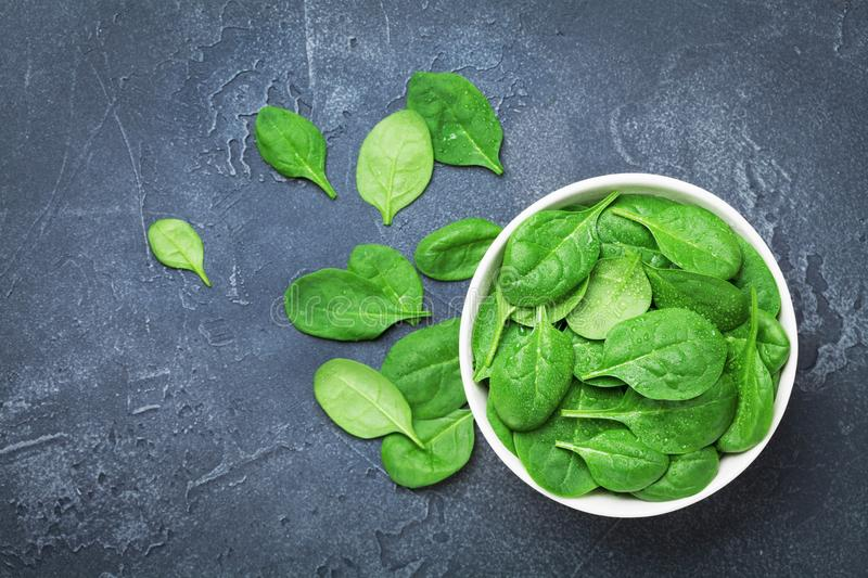 Green spinach leaves in bowl on black table top view. Organic and diet food. royalty free stock photography