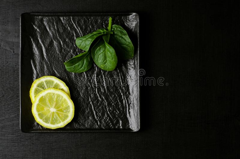 Green spinach and slice of lemon on black plate on black background. Copy space. royalty free stock photography