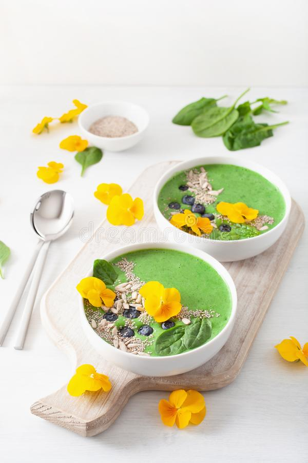 Green spinach smoothie bowl with blueberry, chia seed and edible. Pansy flowers stock image