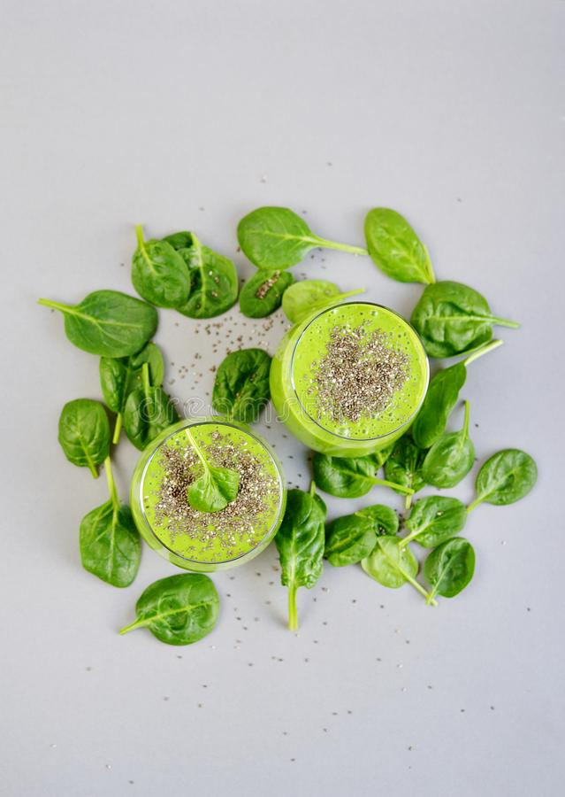 Green spinach smoothies with chia seeds, healthy food concept, detox. Gray background, top view stock photography