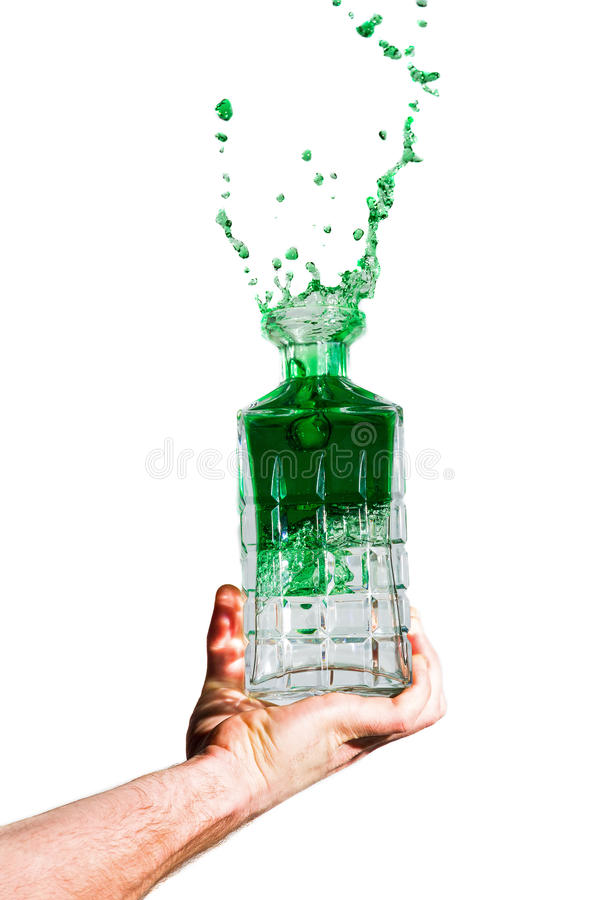 Green splash. Man holding a crystal bottle with green liquid splashing out on a white background stock images