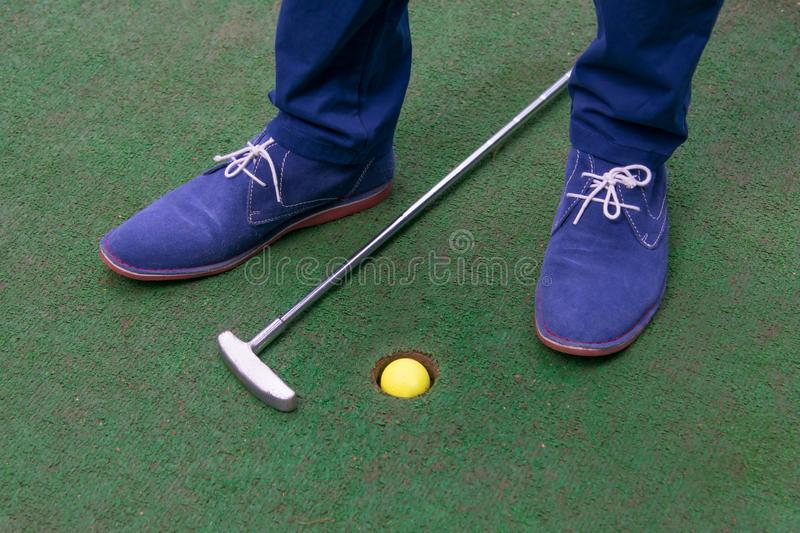Green sport background, mini golf course, a ball in the pocket and a stick royalty free stock image